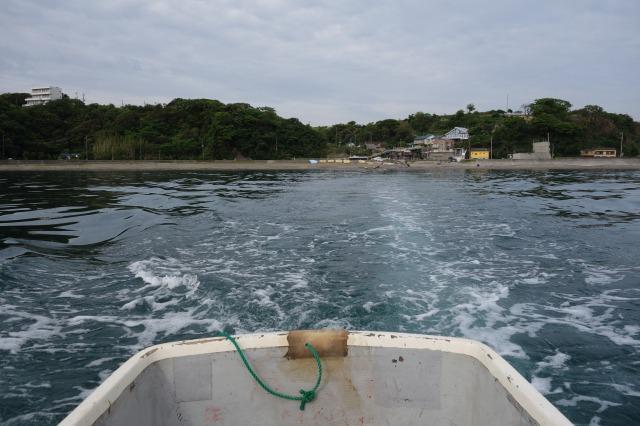 船外機付き小舟により曳かれていく写真